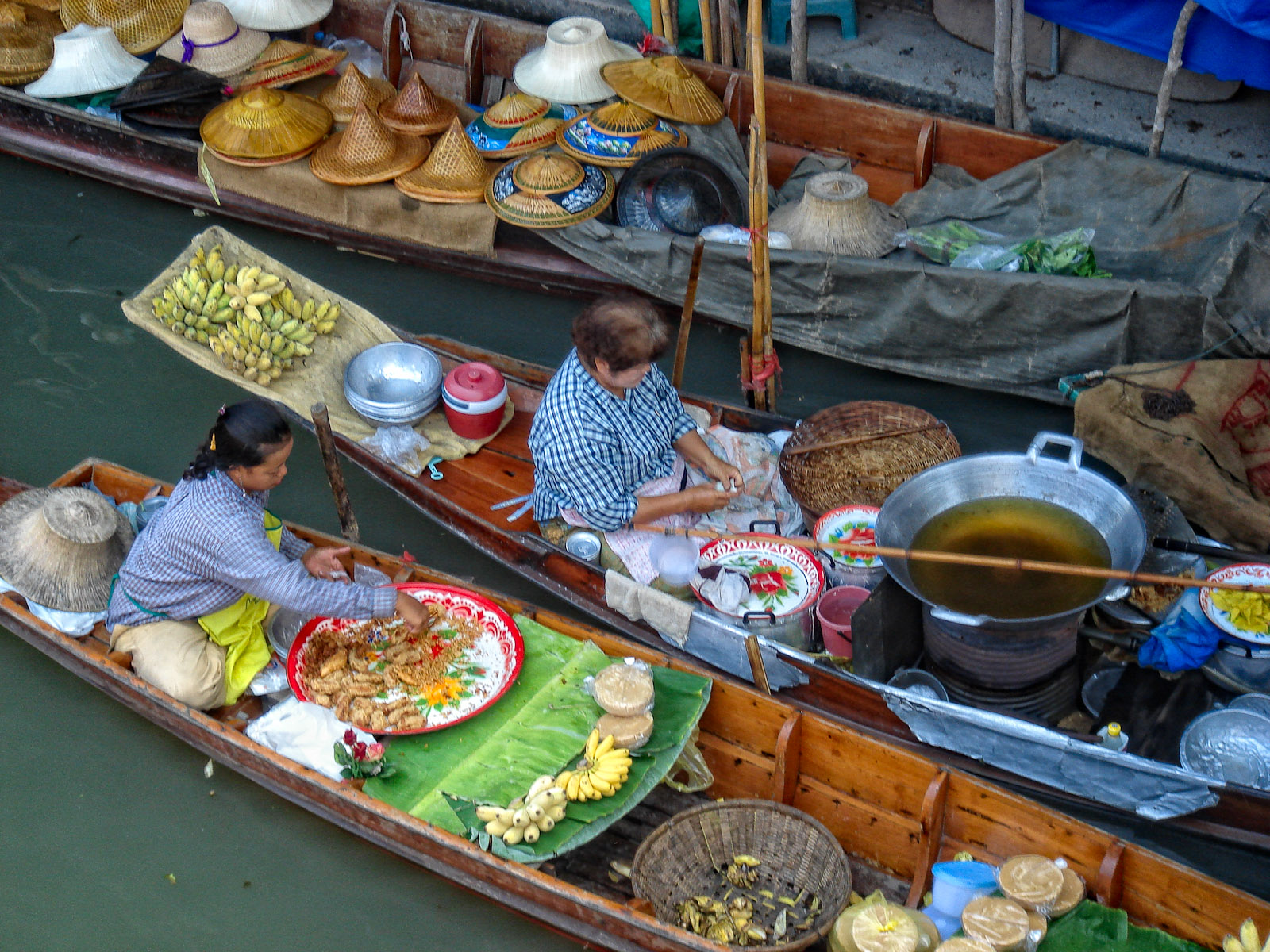 Women prepare food for sale at floating market, Thailand