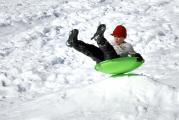 Boy Enjoys Sledding (But he should be wearing protective Headgear!)