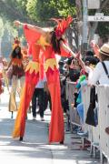 A stilt-walker dressed as Fire high-fives an onlooker in San Francisco's Carnaval parade.