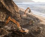 Workers positioning large boulders at the base of a Pacifica cliff in an attempt to prevent further erosion.