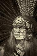 Man with face painted for Dia de Los Muertos and wearing ceremonial Aztec feather headress.