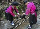 Zhuang minority woman helping her peer to wash her hair, Guangxi, China