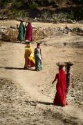Beautiful ladies transporting dirt in the field,India