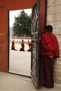 A monk peeping to see others reciting bible with hand gestures